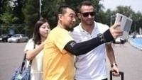 O meia Renato Augusto posando para foto com fã no futebol chinês
