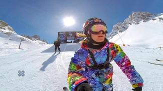 Snowboarder desce no Slopestyle com uma câmera e a aste na mão