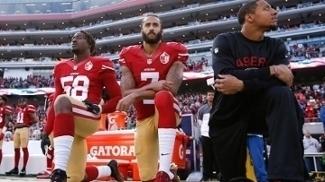 Colin Kaepernick (centro) ajoelhado em protesto durante execução do hino dos EUA