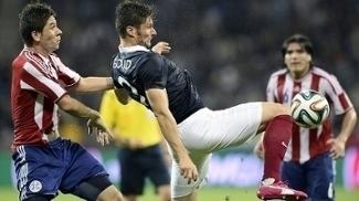 Giroud disputa a bola com Cáceres durante amistoso entre França e Paraguai em 2014