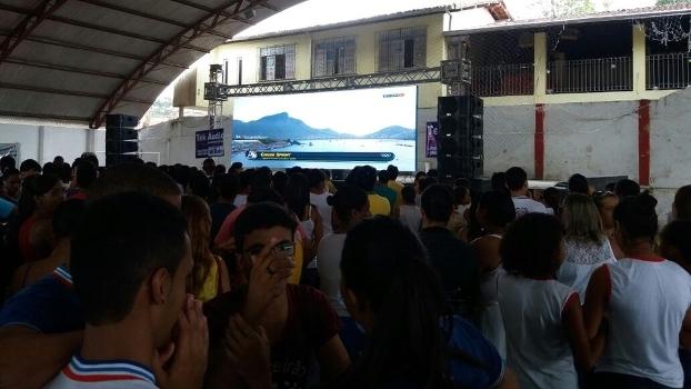 Crianças acompanham no telão montado na escola a prova de Isaquias