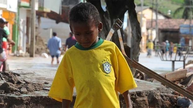 Criança, vítima das enchentes em Murici, em 2010, com a camisa do Brasil