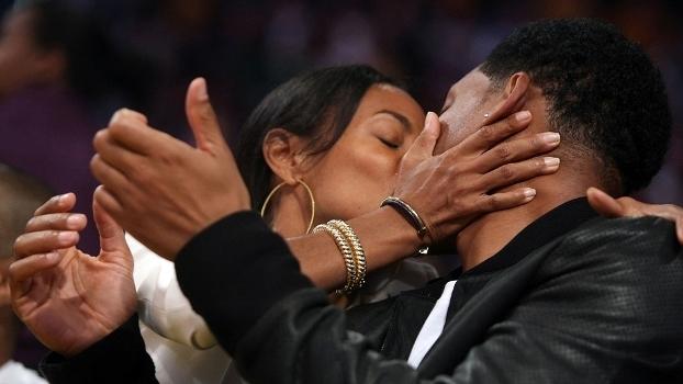 O casal Will Smith e Jada Pinkett mostra que o amor está no ar no jogo entre Sixers e Lakers, em 28 de novembro de 1997
