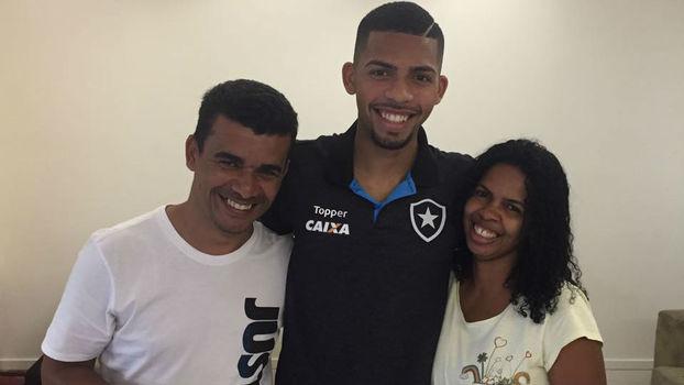 Matheus Fernandes (ao centro) é cercado pelos pais