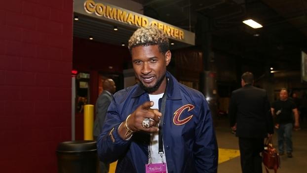 O cantor Usher antes de achar o seu lugar colado à quadra antes do jogo 3 das Finais da NBA