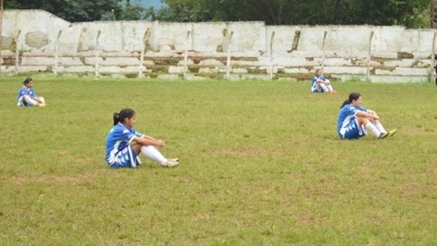Jogadoras do San Lorenzo sentadas em campo durante protesto