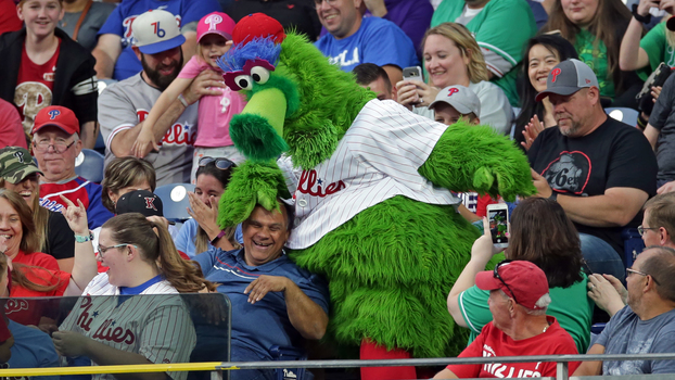 Phillie Phanatic brinca com torcedor do Philadelphia Phillies durante jogo contra o Arizona Diamondbacks