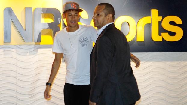 Neymar e seu pai em frente ao logo da NR Sports, empresa que gere a imagem do jogador