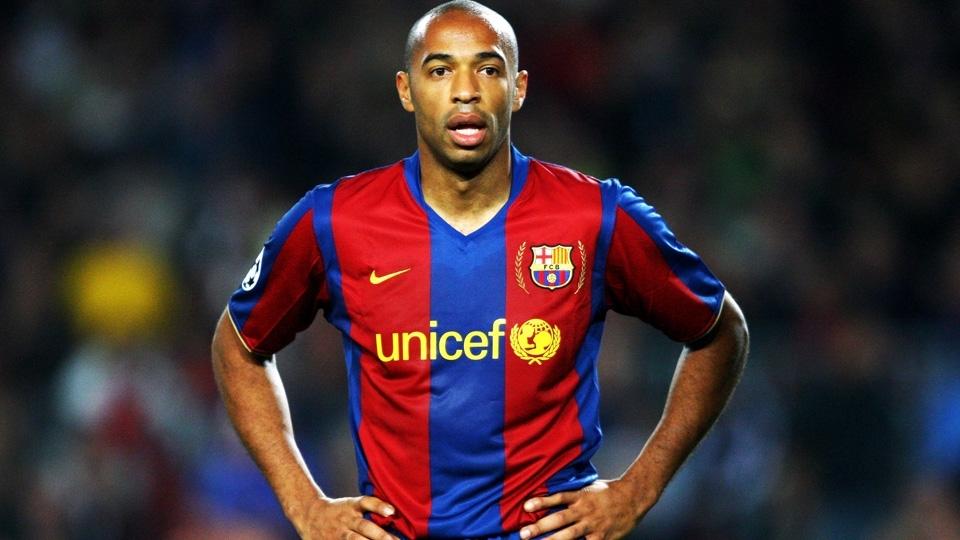 Henry com a camisa 2007/08 do Barcelona: listras médias e com detalhes em dourado em volta do escudo
