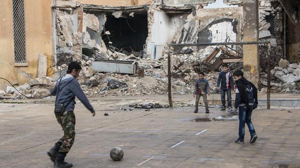 Um soldado da força de oposição joga futebol com crianças em Aleppo, na Síria, em 2014