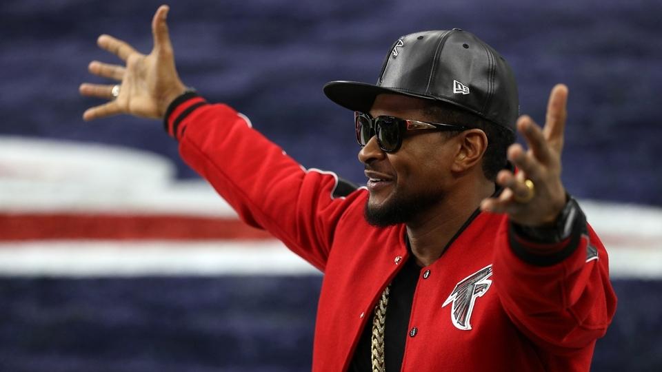 Vestido com as cores do Atlanta Falcons, o rapper Usher entra no gramado antes do Super Bowl LI