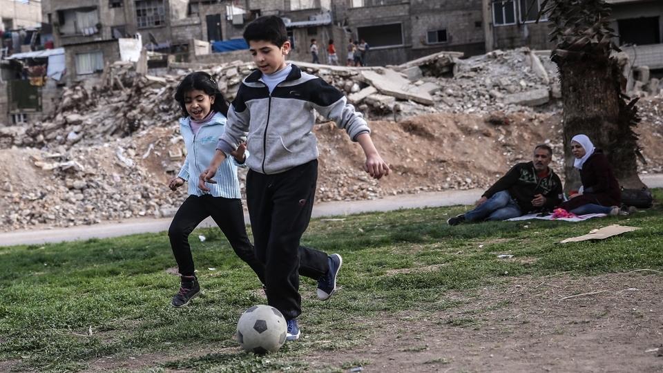 Crianças jogam futebol em um bairro de Damasco, em área liberada após acordo de cessar-fogo entre o exército sírio e rebeldes, em 2016