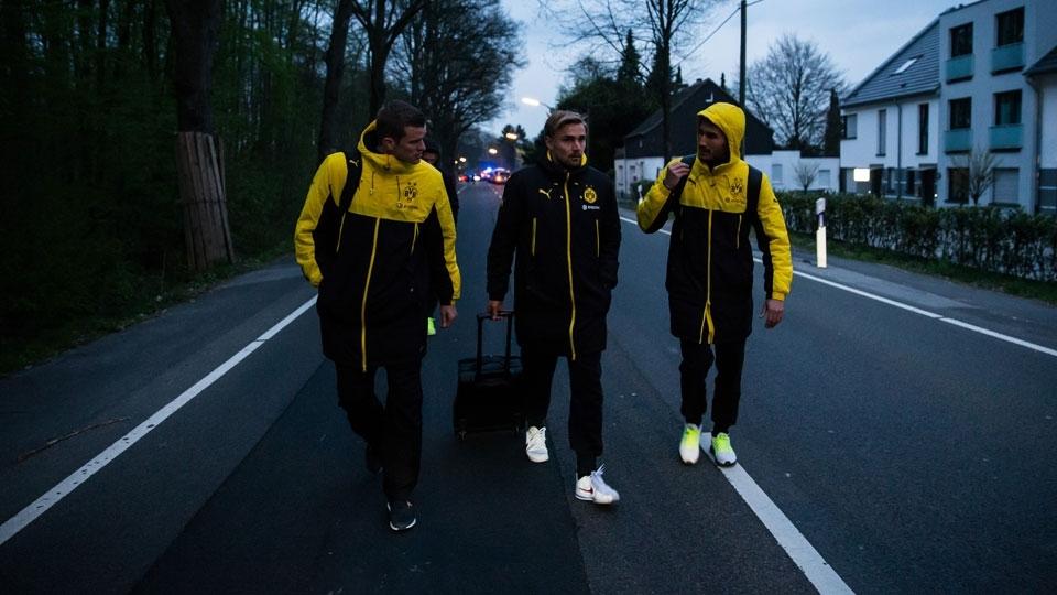 Bender, Schmelzer e Sahin caminham pela rua após deixarem o ônibus