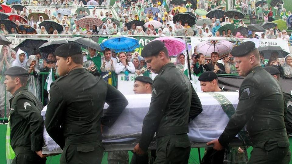 Os caixões foram envoltos em branco e embalados em plástico para protegê-los da chuva torrencial em Chapecó