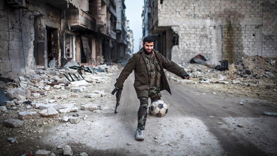 Um opositor ao governo joga futebol em Saif al-Dawlah, na região de Aleppo, na Síria, em 2013