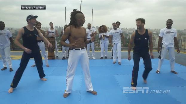 No topo de um prédio, Daniel Ricciardo e Max Verstappen aprendem capoeira e tocam berimbau