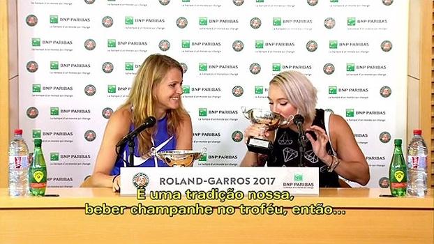 Campeãs em Roland Garros, a dupla Mattek-Sands e Safarova comemora bebendo champagne na taça do torneio